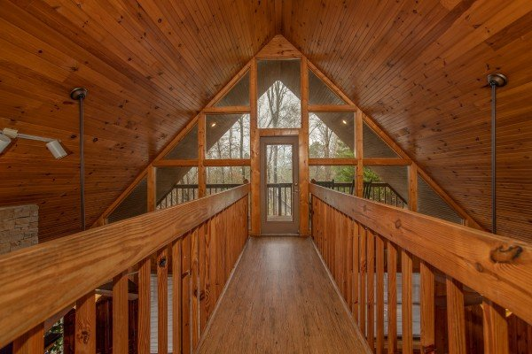 Catwalk on the loft level leading to a private deck at Around the Bend, a 3 bedroom cabin rental located in Pigeon Forge