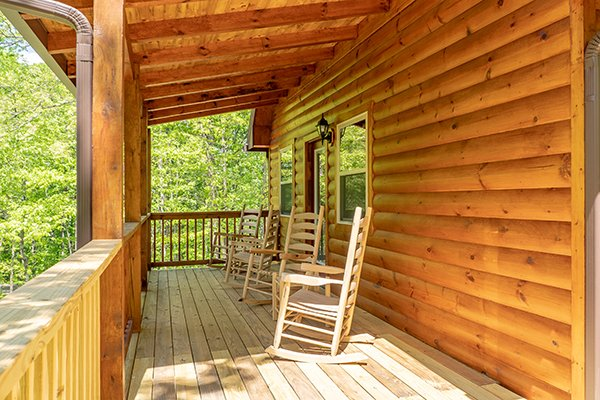 Covered deck with rocking chairs at Relaxation Ridge, a 2 bedroom cabin rental located in Pigeon Forge