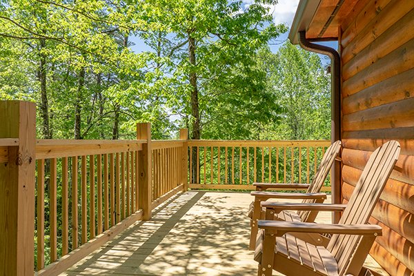 Deck chairs facing a wooded view at Relaxation Ridge, a 2 bedroom cabin rental located in Pigeon Forge