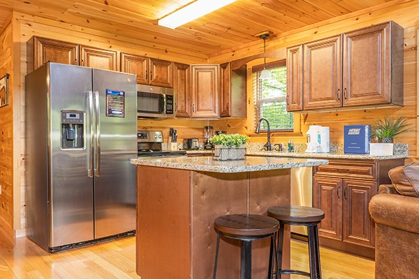 Kitchen island in a kitchen with stainless appliances at Relaxation Ridge, a 2 bedroom cabin rental located in Pigeon Forge