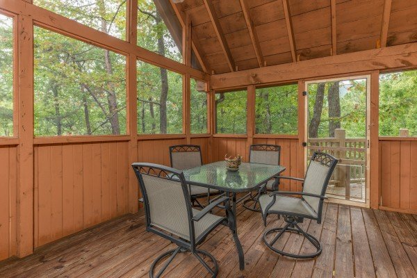 Dining space for four on a screened deck at Yes, Deer, a 2 bedroom cabin rental located in Pigeon Forge