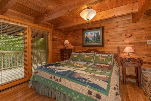 King bed, two night stands, and lamps in a bedroom at Yes, Deer, a 2 bedroom cabin rental located in Pigeon Forge