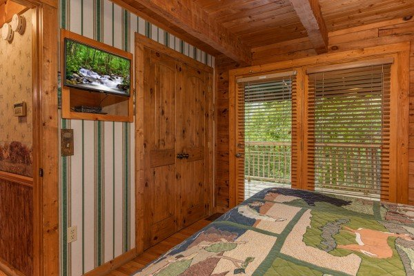 TV and deck access in a bedroom at Yes, Deer, a 2 bedroom cabin rental located in Pigeon Forge