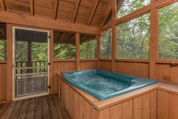 Hot tub on a covered deck at Yes, Deer, a 2 bedroom cabin rental located in Pigeon Forge