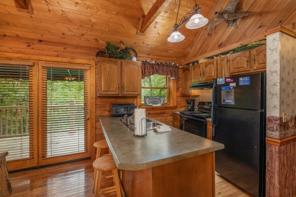 Kitchen with black appliances and breakfast bar at Yes, Deer, a 2 bedroom cabin rental located in Pigeon Forge