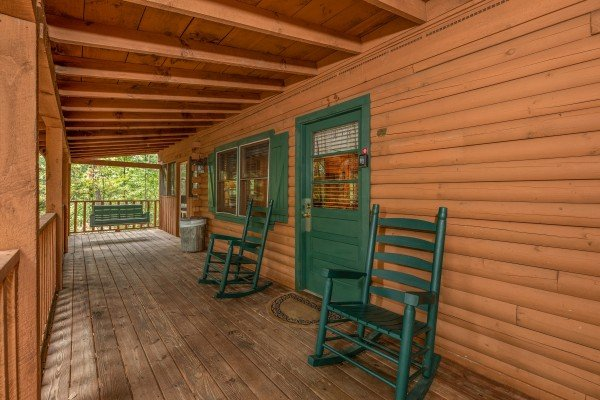 Green rocking chairs on a covered porch at Yes, Deer, a 2 bedroom cabin rental located in Pigeon Forge