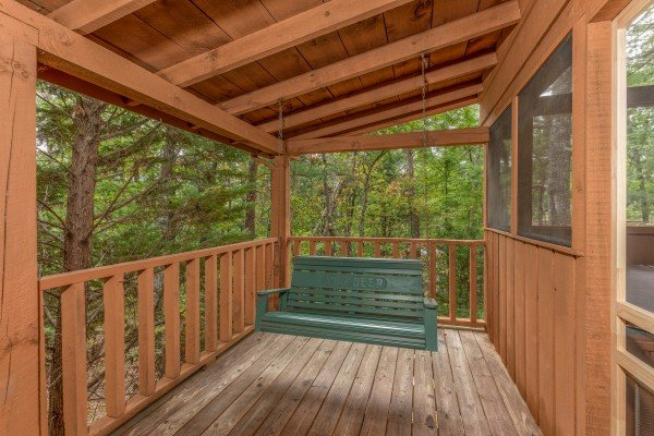 Porch swing on a covered deck at Yes, Deer, a 2 bedroom cabin rental located in Pigeon Forge