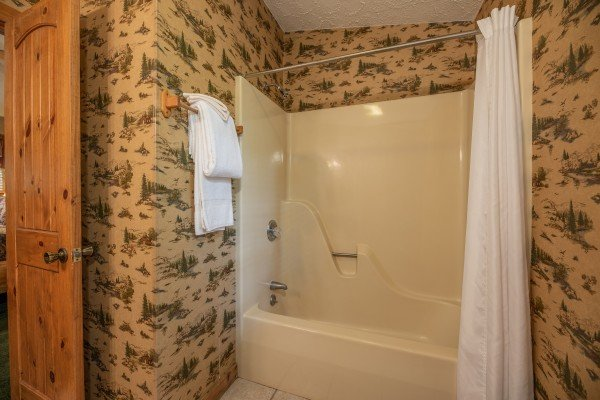 Tub and shower in a bathroom at Yes, Deer, a 2 bedroom cabin rental located in Pigeon Forge