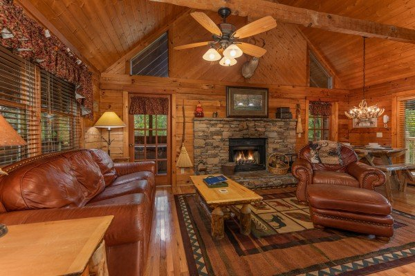 Fireplace and leather sofa and leather chair at Yes, Deer, a 2 bedroom cabin rental located in Pigeon Forge