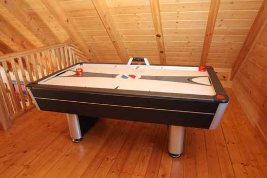lofted game room has an air hockey table at cedar creeks a 2 bedroom cabin rental located in douglas lake