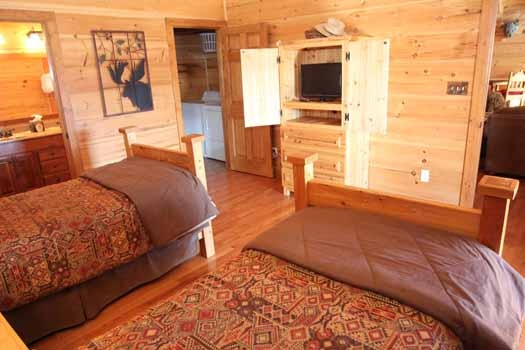 bedroom with hidden tv at foot of beds at cedar creeks a 2 bedroom cabin rental located in douglas lake