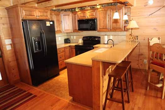 kitchen with bar and stools at cedar creeks a 2 bedroom cabin rental located in douglas lake