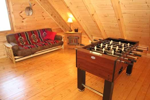 foosball table and futon in the lofted game room at cedar creeks a 2 bedroom cabin rental located in douglas lake