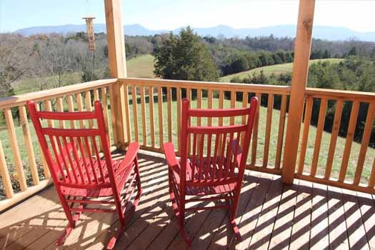 red rocking chairs on the deck at cedar creeks a 2 bedroom cabin rental located in douglas lake