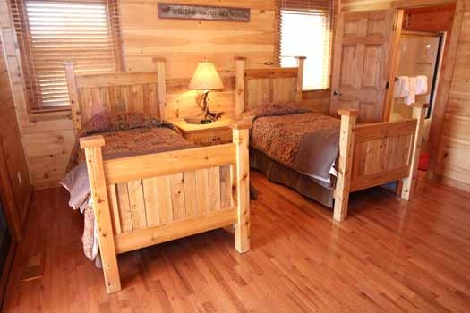two twin beds in a bedroom at cedar creeks a 2 bedroom cabin rental located in douglas lake