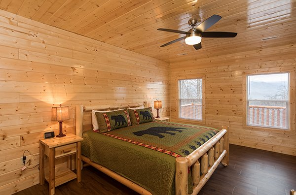 Bedroom with a king log bed at Splash Mountain Lodge a 4 bedroom cabin rental located in Gatlinburg