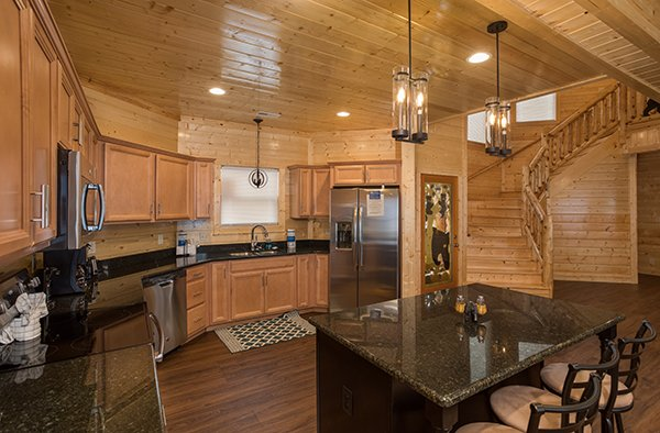 Island with counter seating and kitchen with stainless appliances at Splash Mountain Lodge a 4 bedroom cabin rental located in Gatlinburg