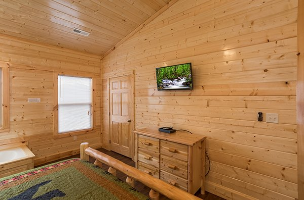 Dresser, TV, and jacuzzi in a bedroom at Splash Mountain Lodge a 4 bedroom cabin rental located in Gatlinburg