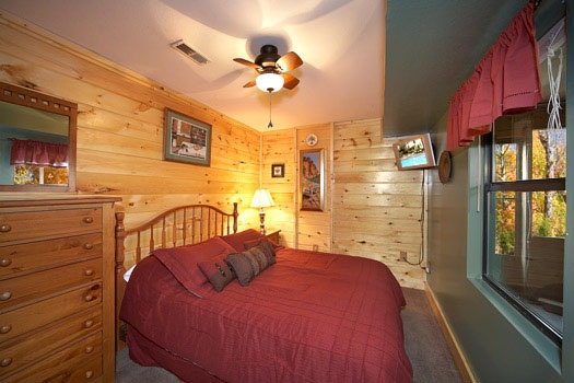 first floor bedroom with queen size bed at raccoon's rest a 2 bedroom cabin rental located in pigeon forge