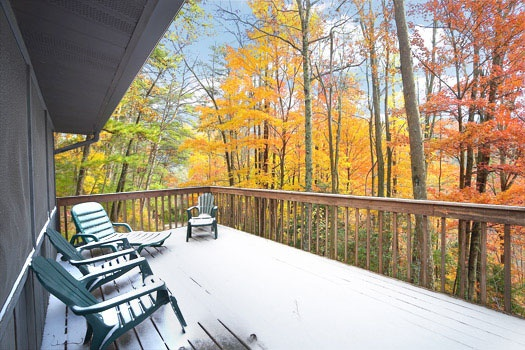 Main level deck with seating at Raccoon's Rest, a 2 bedroom cabin rental located in Pigeon Forge