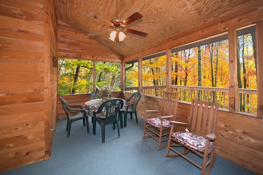 Screen porch with patio table and rockers at Raccoon's Rest, a 2 bedroom cabin rental located in Pigeon Forge