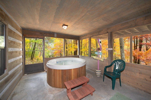 Screened porch with hot tub at Raccoon's Rest, a 2 bedroom cabin rental located in Pigeon Forge