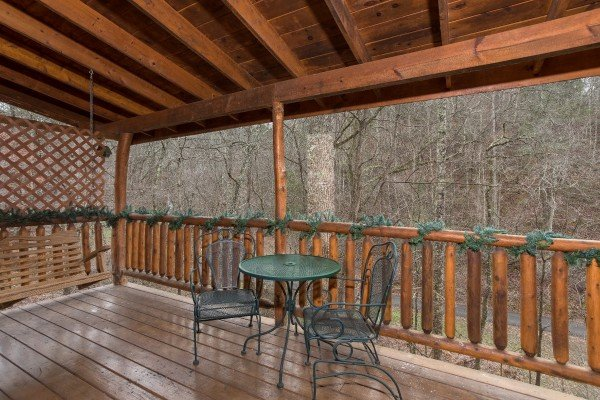 Dining table on a covered deck at Gettin' Lucky, a 1-bedroom cabin rental located in Gatlinburg