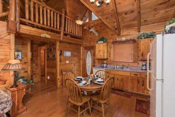 Dining table for four in a kitchen with white appliances at Gettin' Lucky, a 1-bedroom cabin rental located in Gatlinburg