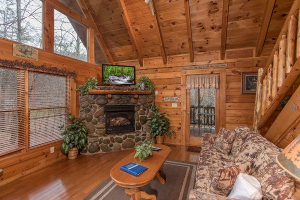 Looking at the stone fireplace and large living room windows at Gettin' Lucky, a 1-bedroom cabin rental located in Gatlinburg