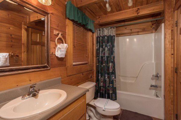 Bathroom with a tub and shower at Gettin' Lucky, a 1-bedroom cabin rental located in Gatlinburg