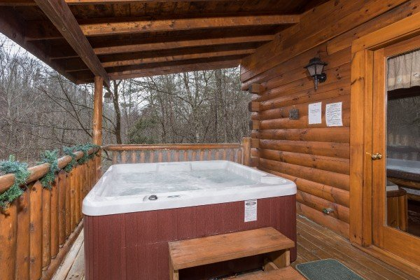 Hot tub on a covered deck at Gettin' Lucky, a 1-bedroom cabin rental located in Gatlinburg