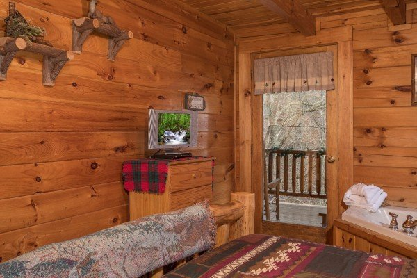 Dresser, TV, in-room jacuzzi, and deck access at Gettin' Lucky, a 1-bedroom cabin rental located in Gatlinburg