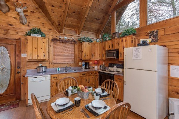 Dining space for four in a kitchen with white appliances at Gettin' Lucky, a 1-bedroom cabin rental located in Gatlinburg