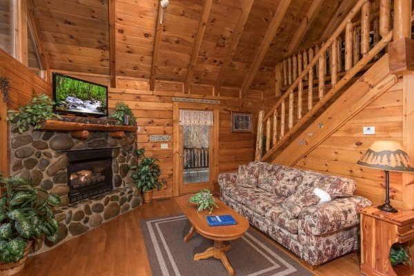 Living room with a river stone fireplace and TV at Gettin' Lucky, a 1-bedroom cabin rental located in Gatlinburg