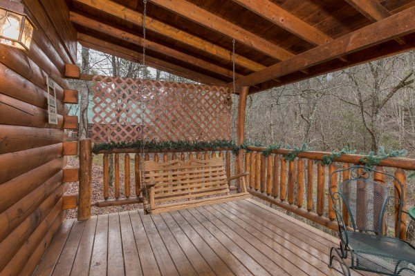 Swing on the covered porch at Gettin' Lucky, a 1-bedroom cabin rental located in Gatlinburg