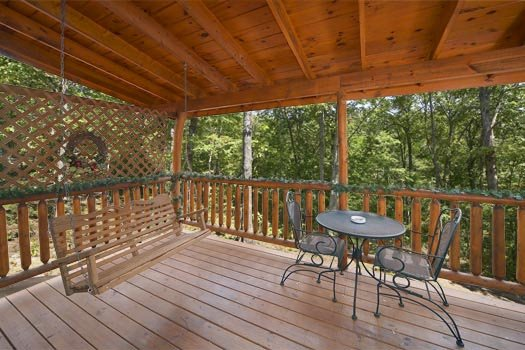 Patio furniture and swing on the deck at Gettin' Lucky, a 1-bedroom cabin rental located in Gatlinburg