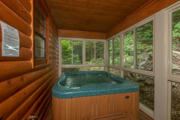 Hot tub on a screened porch at Time to Pause, a 2 bedroom cabin rental located in Pigeon Forge