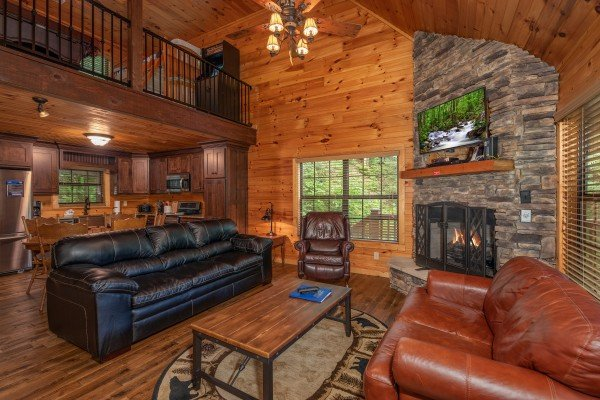 Living room with sofa, loveseat, fireplace, and TV at Time to Pause, a 2 bedroom cabin rental located in Pigeon Forge