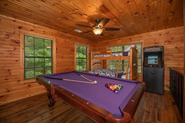 Purple felt pool table, bunk beds, and arcade game at Time to Pause, a 2 bedroom cabin rental located in Pigeon Forge