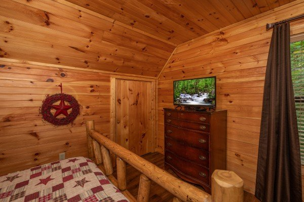 Dresser and a TV in a bedroom at Time to Pause, a 2 bedroom cabin rental located in Pigeon Forge