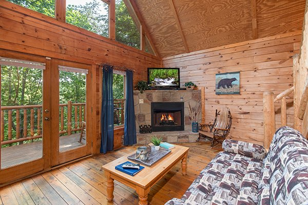 Living room with fireplace, TV, and large windows at My Blue Heaven, a 1 bedroom cabin rental located in Gatlinburg