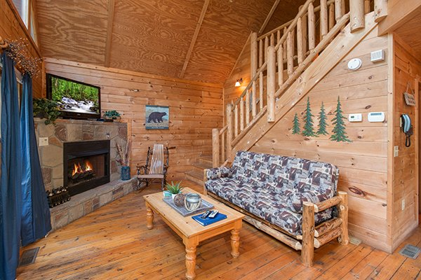 Futon, fireplace, and TV in the living room at My Blue Heaven, a 1 bedroom cabin rental located in Gatlinburg