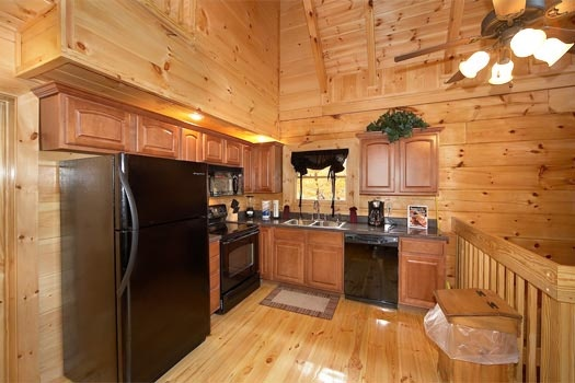 kitchen with black appliances at settlin' inn a 3 bedroom cabin rental located in gatlinburg