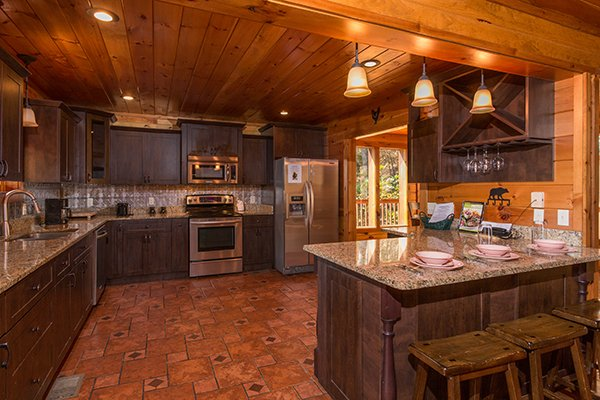 Kitchen with stainless appliances and breakfast bar at Rocky Top Lodge, a 3 bedroom cabin rental located in Pigeon Forge