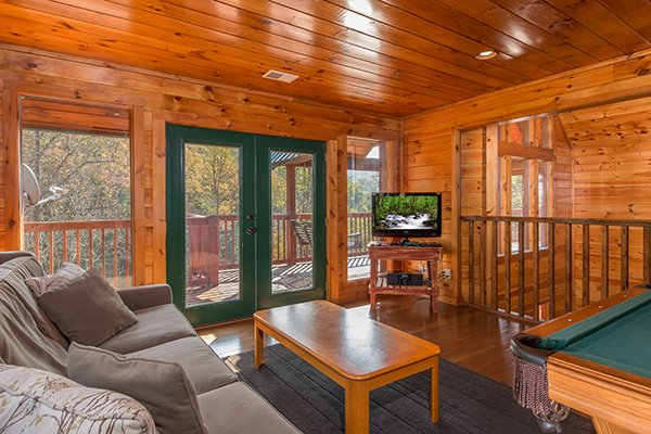 Game room with sleeper sofa, deck access, and TV at Rocky Top Lodge, a 3 bedroom cabin rental located in Pigeon Forge