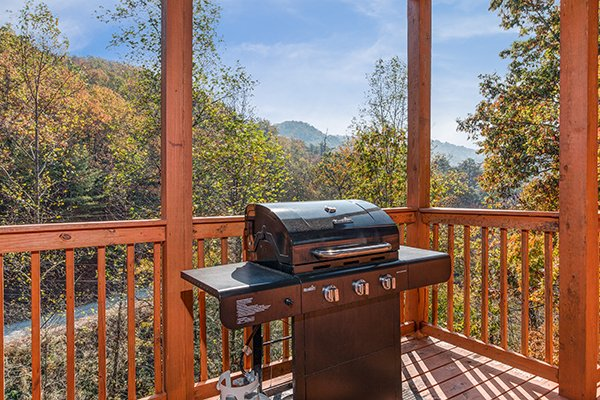 Propane grill on a covered deck at Rocky Top Lodge, a 3 bedroom cabin rental located in Pigeon Forge