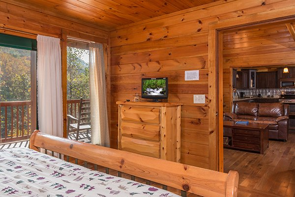 Bedroom with dresser, TV, and deck access at Rocky Top Lodge, a 3 bedroom cabin rental located in Pigeon Forge