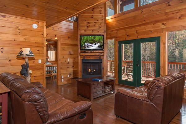 Living room with fireplace, TV, and deck access at Rocky Top Lodge, a 3 bedroom cabin rental located in Pigeon Forge
