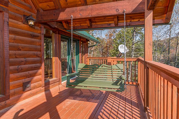 Porch swing on a covered deck at Rocky Top Lodge, a 3 bedroom cabin rental located in Pigeon Forge