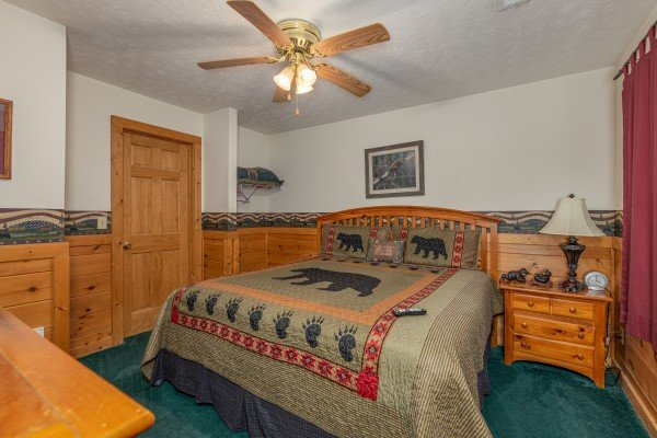King bed, night stand, and a lamp in a bedroom at Cub's Crossing, a 3 bedroom cabin rental located in Gatlinburg